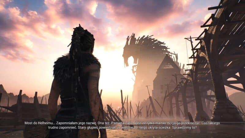 Hellblade: Senua's Sacrifice bohaterka stoi obok mostu i obserwuje twierdzę Hel, na ekranie widoczny tekst narratorki
