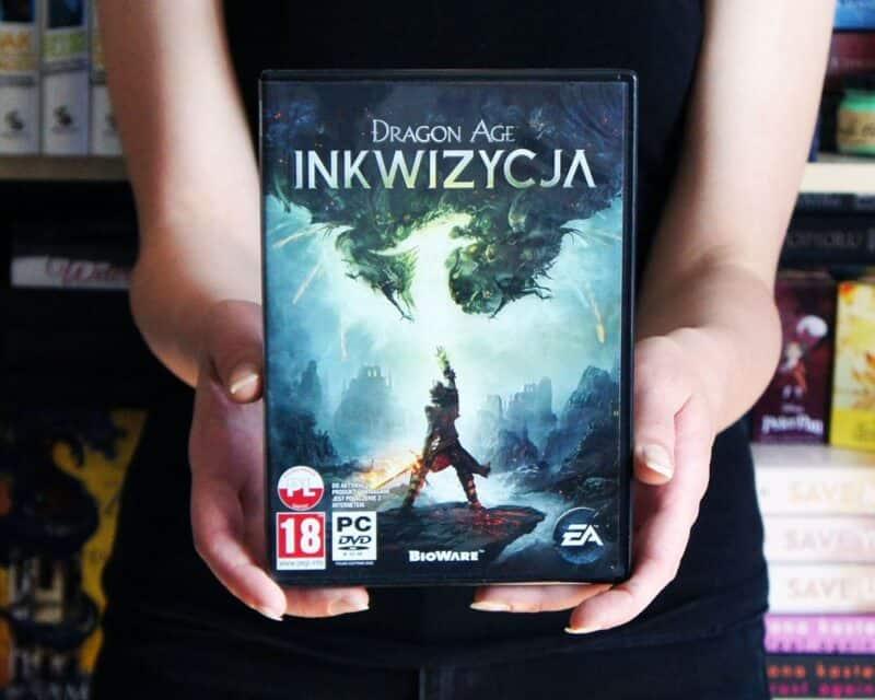 Kobieta trzymająca wydanie pudełkowe gry Dragon Age Inkwizycja.