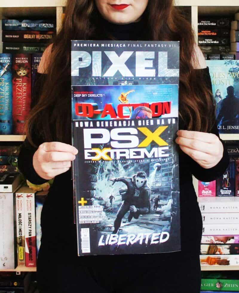 Kobieta trzyma trzy czasopisma o grach.